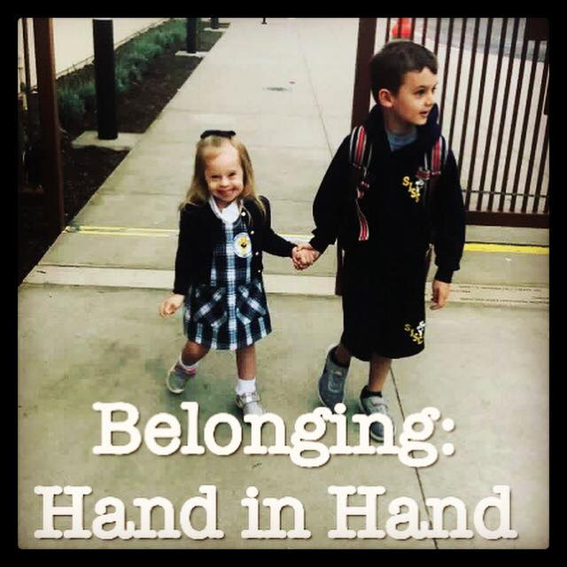 A big brother holding the hand of his little sister as they walk into school.