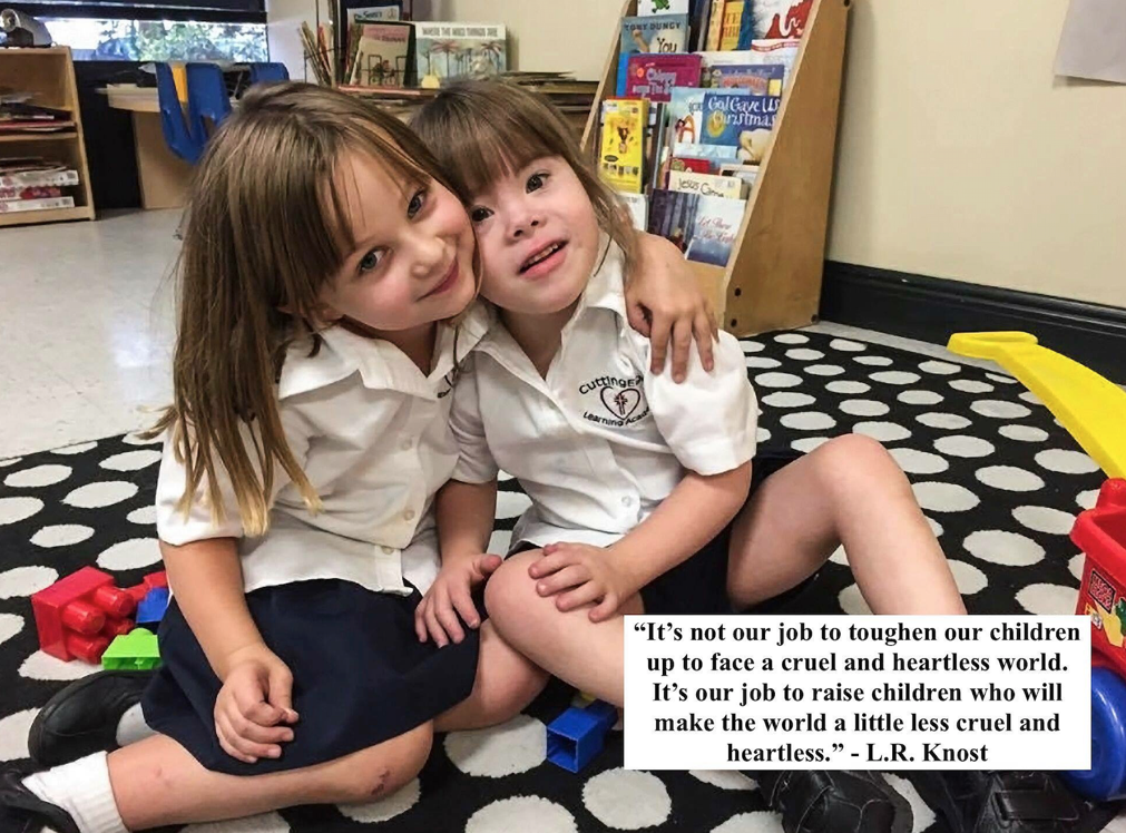 Two kindergarten age girls wearing white shirts and navy skorts as a uniform are hugging on the carpet looking at the camera. The quote: It's not our job to toughen our children up to face a cruel and heartless world. It's our job to raise children who will make the world a little less cruel and heartless. - L.R.Knost