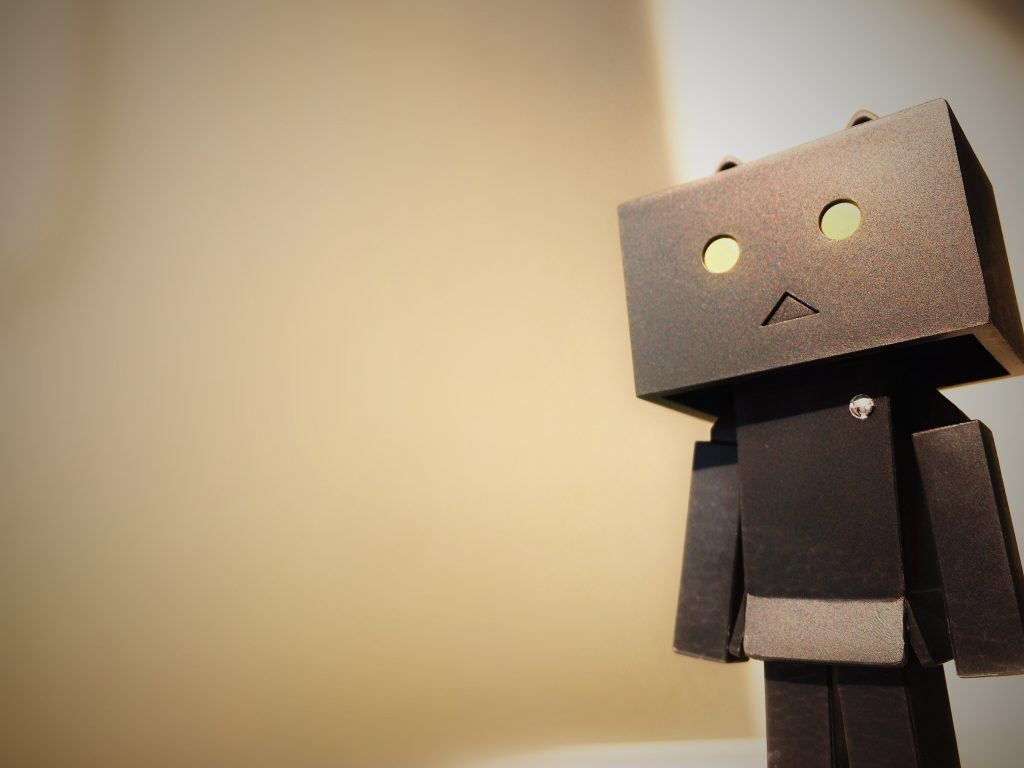an anime style 3d robot sculpture made from cardboard with a sad face and lit eyes